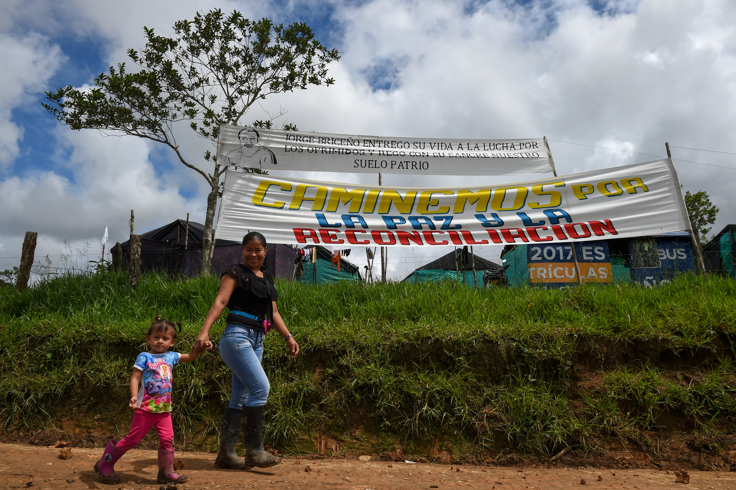 A rebel woman and a girl walk past a sign at the Transitional Standardization Zone Mariana Paez, Buena vista, Mesetas municipality, Colombia on June 26, 2017, before the final ceremony of abandonment of arms and the FARC's end as an armed group. / AFP PHOTO / RAUL ARBOLEDA